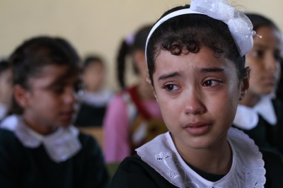 Palestinian children show the distress on their faces caused by the war crimes of Israel's terrorist military assault that targeted civilian homes and buildings. (Photo (C) Copyright 2014 Mohammed Asad and may be used with full attribution to Mohammed Asad and The Arab Daily News.)