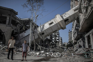 Palestinians walk next to the collapsed minaret of mosque in Gaza City, Gaza Strip, 30 July 2014. The mosque was destroyed in an overnight Israeli airstrike.  EPA/OLIVER WEIKEN and Amnesty International