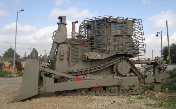 Caterpillar D9 Tractor parked outside an Israeli settlement on lands confiscated by Israel from Palestinian civilians (Wikipedia)