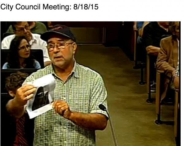 Chaldean protestor opposing the building of a Mosque in Sterling Heights holds up image of a woman in a burqa as a reason why (screen capture from the Sterling Heights City Video.)