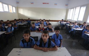 Children sit attentively in almost barren classrooms during the first day of school. Supplies have been blocked by Israel's oppressive embargo.  Copyright (C) 2015 Mohammed Asad. All Rights reserved. Photos may be reproduced with proper credit to Mohammed Asad and the Arab Daily News