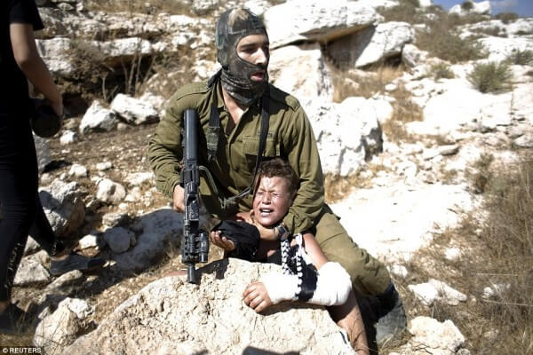 Reuters image of a Palestinian boy being held by Israeli soldiers has become the focus on a media debate and Israeli accusations of bias