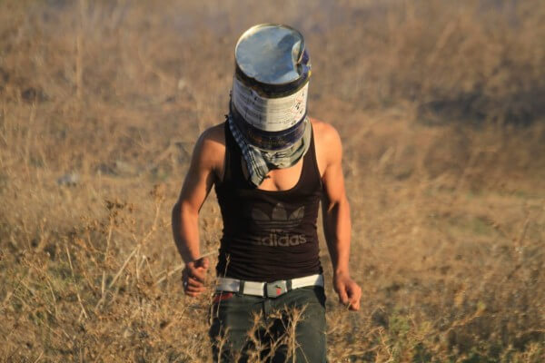 A Palestinian puts a metal can over his head to protect himself from the gas canisters being fired by the Israeli soldiers Copyright (C) 2015 Tarek Masood. All Rights Reserved