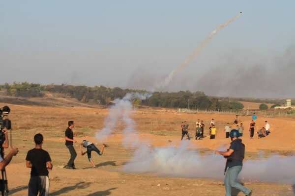 Palestinian protestor throws back a gas canister fired by heavily armed Israeli soldiers who hide behind their defenses on the border of Al Bureij in the Gaza Strip. Copyright (C) 2015 Tarek Masood. All Rights Reserved