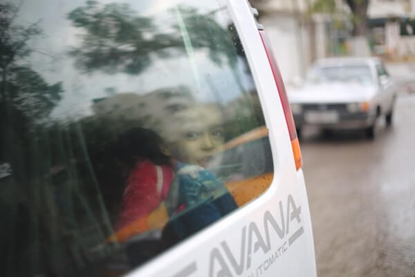 Girl peers anxiously out of the back window of a van. Copyright (C) 2015 Tarek Masood. All Rights Reserved