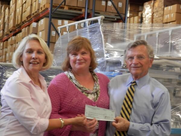 Sue Drinan (left) and Greg Drinan (right) present funds raised for the hospital