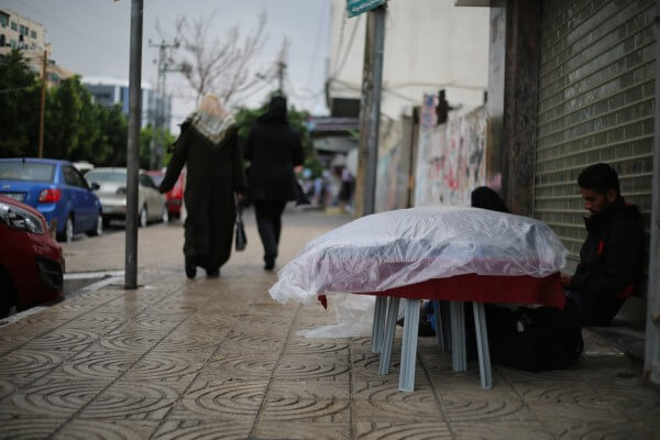 Rain blankets the Gaza Strip as a street merchant covers his food and a couple walk down the Gaza street. Copyright (C) 2015 Tarek Masood. All Rights Reserved