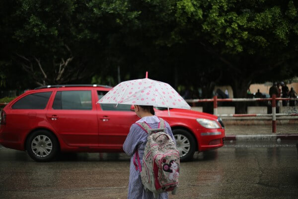 Palestinian girl waits for a car to move during a recent rain. Copyright (C) 2015 Tarek Masood. All Rights Reserved