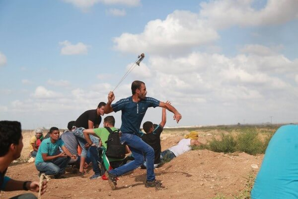Palestinians in the Gaza Strip near Shujaiya throw stones back at Israeli soldiers who fire live weapons from the border. Copyright (C) Tarek Masood 2015. All Rights Reserved