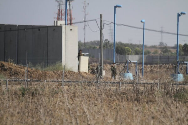 Israeli soldiers with their automatic weapons fire from behind barricades and fences along the border of the Gaza Strip near Shujaiya at Palestinian civilians provoking them to respond with their only weapon, stones. Copyright (C) Tarek Masood 2015. All Rights Reserved