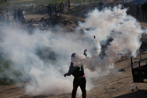 Civilians overwhelmed by tear gas and metal bullets fired by Israel in the Gaza Strip. Copyright (C) 2015 Mohammed Asad. All Rights reserved. Photos may be reproduced with proper credit to Mohammed Asad and the Arab Daily News