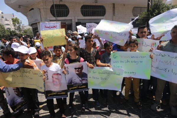 Palestinian demonstrators hold posters of Mohammad El Halabi, World Vision's manager of operations in Gaza who was accused by Israel of funnelling millions of dollars in aid money to Hamas, during a protest in solidarity with El Halabi, organised by foundations and societies benefiting from World Vision in Gaza City August 7, 2016. Photo by Mohammed Asad