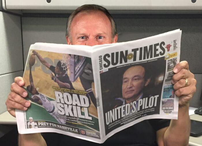 "Illinois' incompetent Gov. Bruce Rauner ""reading"" the Chicago Sun-Times, one of the worst and most racist newspapers in America. A former owner, critics say Rauner still controls it. Meme and photo courtesy of Ray Hanania"