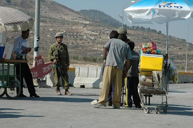 An Israeli soldier buys from Palestinian child...