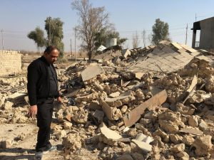 A Catholic church ruined by ISIS in Karamdes, Iraq, is examined by a priest following the predominately Christian town's liberation. (PRNewsfoto/Knights of Columbus)