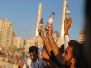 Palestinian athletes send messages of hope in plastic bottles in sea during marathon for the disabled. Photo copyright Ahmad Hasaballah. All Rights reserved.