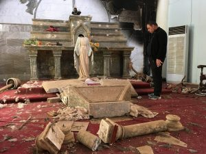 A priest examines the ruins, including a decapitated statue of Mary, in the Catholic church in Karamdes, Iraq, following the town's liberation from ISIS. (PRNewsfoto/Knights of Columbus)