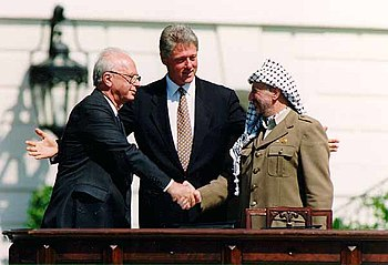 Yitzhak Rabin and Yasir Arafat shake hands at 1993 White House peace signing with President Clinton. Photo courtesy of Wikipedia