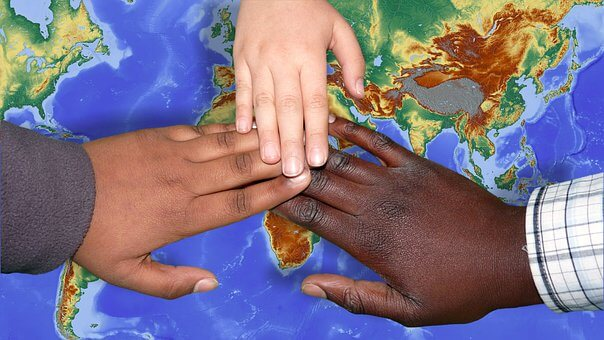White, Black, Brown hands on map of North Africa