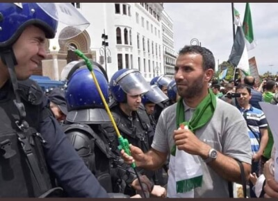 Algiers marcher refreshes riot police Source Saïd Touati. Photo courtesy of Abdennour Toumi